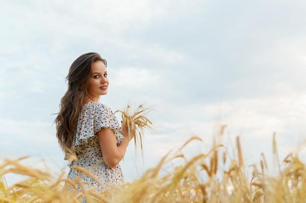 Frau hält weizenohren in händen, sommerfeld. schönes mädchen auf gelber wiese.