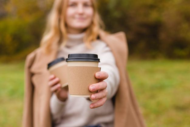 Frau hält zwei papierkaffeetassen