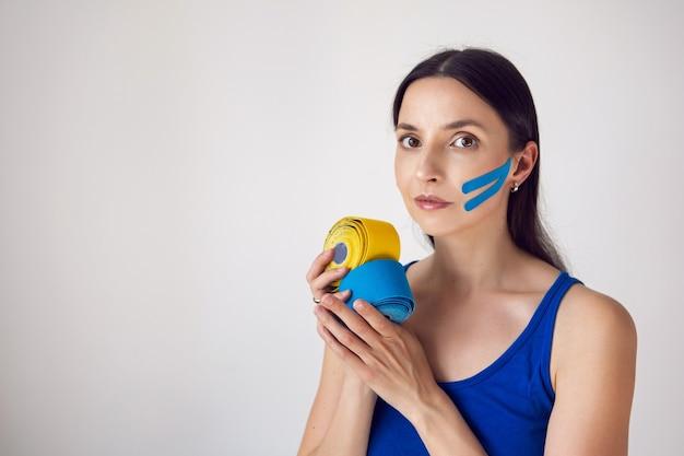 Frau hält zwei stränge kinesio-tape in der hand gelb und blau