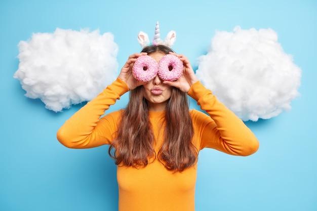 Frau hält zwei süße gebackene donuts auf den augen hält die lippen gefaltet genießt leckeres kalorienreiches essen, gekleidet in orangefarbenen pullover isoliert auf blau