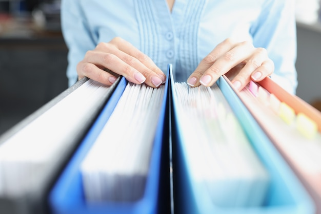 Frau hände auf ordnern mit dokumenten