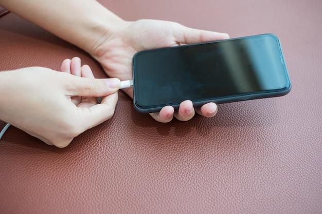 Frau hände, die batterie im mobilen smartphone im sofa zu hause aufladen. technologie-, multiple-sharing- und lifestyle-konzepte