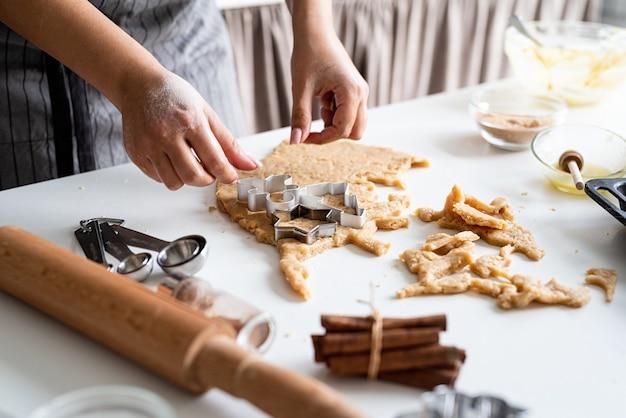 Frau hände, die kekse an der küche backen
