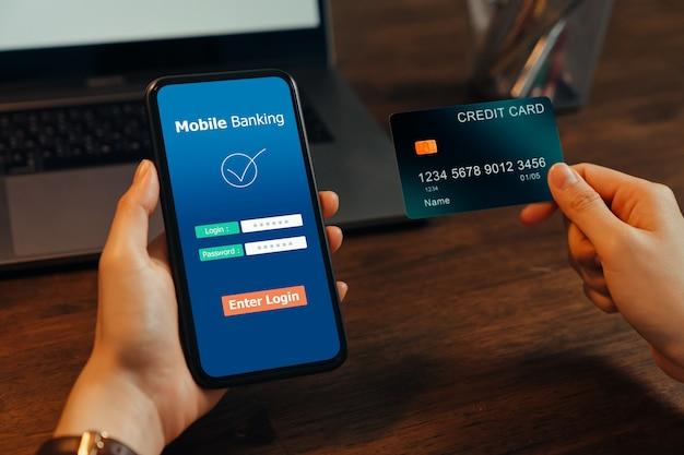 Frau hände, die mobile banking auf smartphone mit kreditkarte halten und passwort eingeben, um anwendung anzumelden.