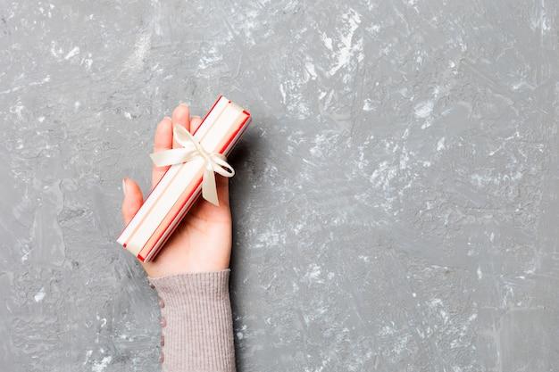 Frau hände halten geschenk verpackt und dekoriert mit schleife auf grauem zement