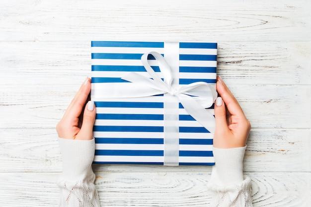 Frau hände halten geschenk verpackt und mit schleife verziert