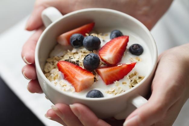 Frau hände halten schüssel mit leckeren müsli mit früchten, hafer und joghurt. nahansicht. gesundes essen konzept.