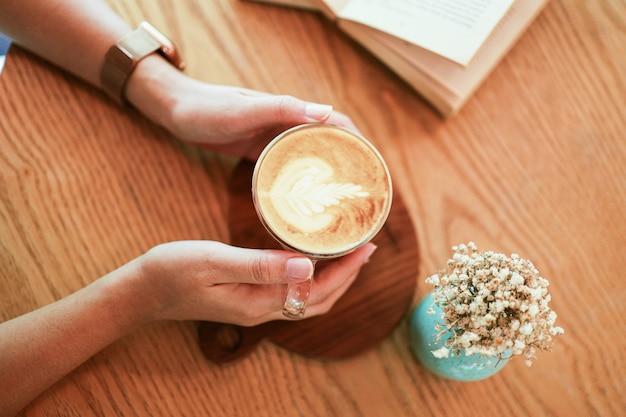 Frau hände halten tasse kaffee mit latte art. morgens eine tasse tee oder kaffee halten.