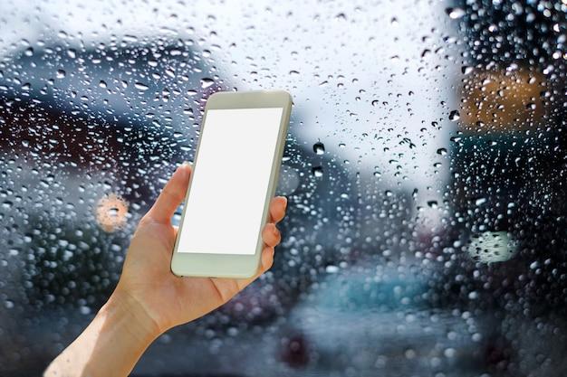 Frau hände mit smartphone mit auf regen tröpfchen am glasfenster mit der stadt