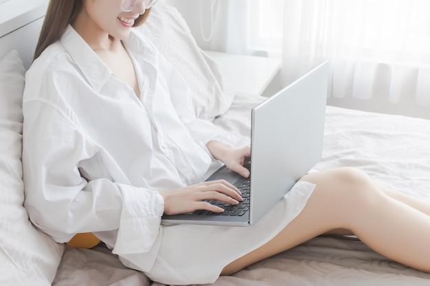 Frau hände typ auf der tastatur der laptop-computer im schlafzimmer, zu hause arbeiten