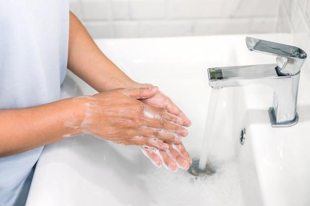 Frau händewaschen, um die ausbreitung von coronavirus sowie erkältung, grippe und bakterien zu hause zu verhindern