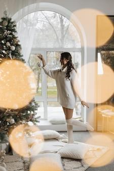 Frau hängt ein spielzeug an einem weihnachtsbaum