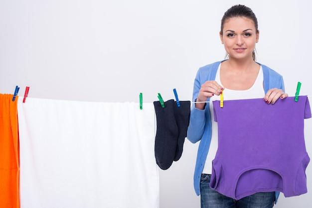 Frau hängt kleidung an wäscheleine.