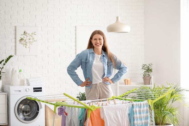 Frau hängt saubere kleidung am trockner in der waschküche
