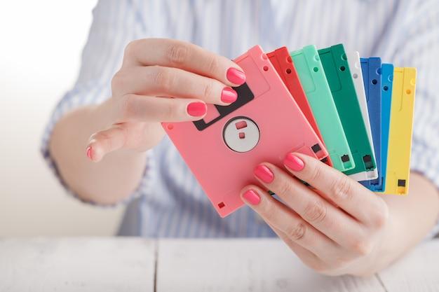 Frau halten alte diskette und modernes flash-laufwerk