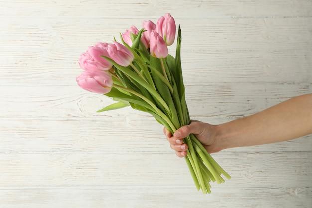 Frau halten blumenstrauß von tulpen auf hölzernem hintergrund, nah oben