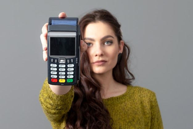 Frau halten modernes bankzahlungsterminal, um zu erwerben, kreditkartenzahlungen zu erwerben