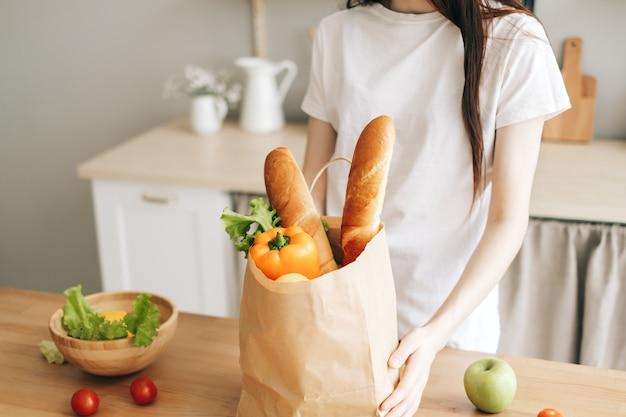 Frau halten öko-einkaufstasche mit frischem gemüse und baguette in der modernen küche