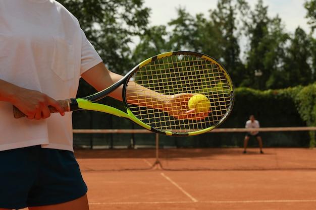 Frau halten schläger und tennisball auf sandplatz