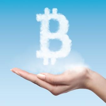 Frau halten symbol bitcoin gemacht von einer wolke auf einem blauen hintergrund, virtuelles geldkonzept.