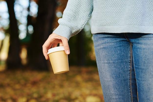 Frau halten tasse kaffee zum mitnehmen im herbstpark