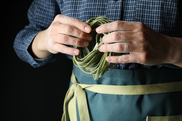 Frau halten ungekochte grüne nudeln, nahaufnahme
