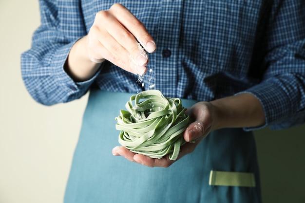 Frau halten ungekochte grüne nudeln und streuen mehl