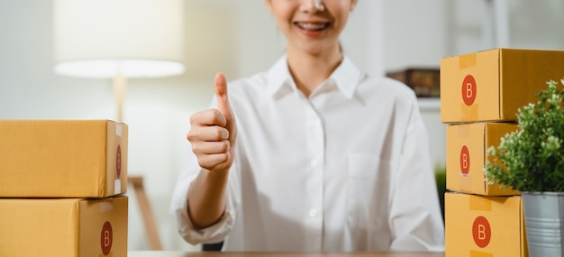 Frau hand, die daumen hoch zeichen und lächelnd und verpackungsbox lieferprodukte zu kunden auf dem tisch macht.
