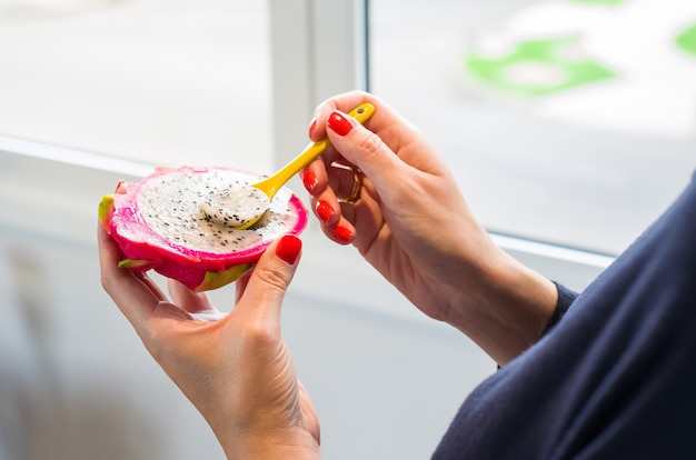 Frau hand, die pitaya mit farbigem löffel isst.