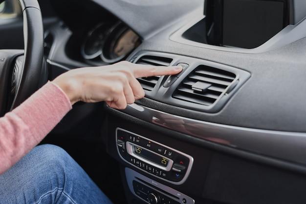 Frau hand drücken not-aus-knopf im auto