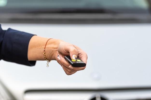 Frau hand hält die auto-fernbedienung, er drückt die fernbedienung, um die autotür zu öffnen