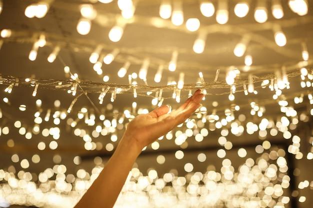 Frau hand hält string vintage warm led weihnachtsbeleuchtung mit verschwommenen und bokeh hintergrund