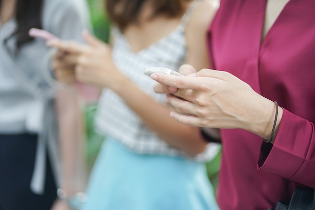 Frau hand halten smartphone-gerät für die arbeit und anwendung mit freunden spielen