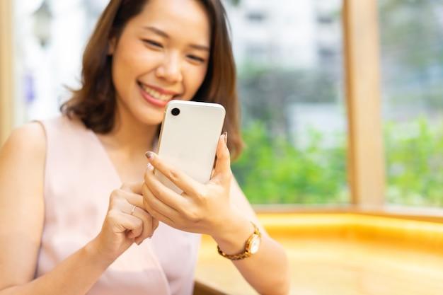Frau hand halten smartphone, um anwendung zu spielen und inhalte auf social-media-netzwerk zu lesen