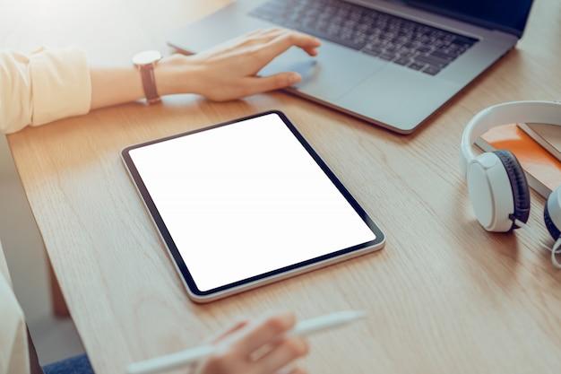 Frau hand halten tablette und digitalen stift mit leerem kopierraum bildschirm für ihre werbung. laptop auf dem tisch im büro.