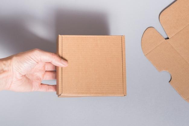 Frau hand holns braunen karton auf grauem hintergrund
