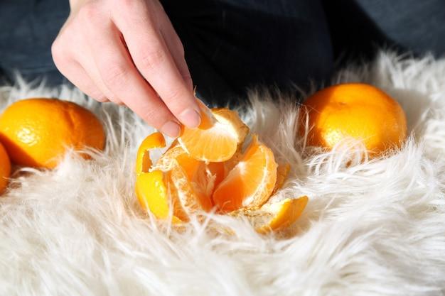 Frau hand peeling reife süße mandarine, nahaufnahme