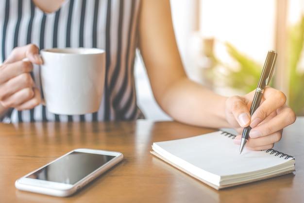 Frau hand schreibt auf einen notizblock mit einem stift.