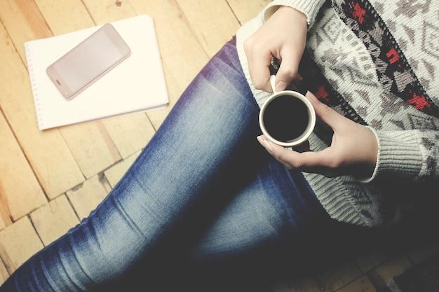 Frau handtelefon kaffee notizbuch und stift auf dem boden