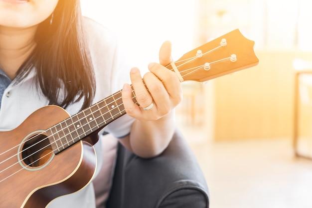 Frau handwerk spielt ukulele