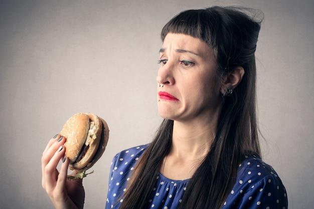 Frau hat angst vor einem großen hamburger