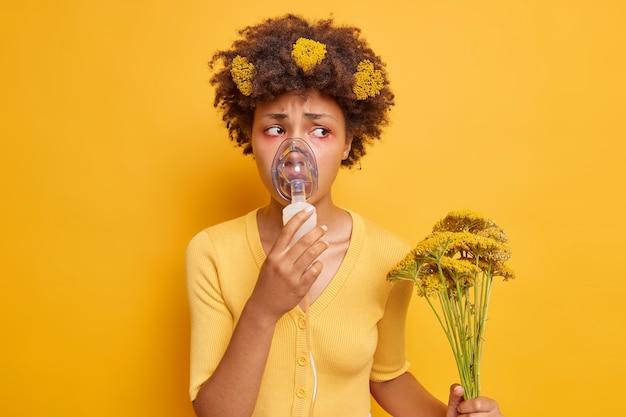 Frau hat asthmaanfälle gesundheitliche probleme trägt eine sauerstoffmaske, die beim atmen hilft hält wildblumen, die allergische reaktionen verursachen, hat rote, geschwollene augen, die über einer gelben wand isoliert sind