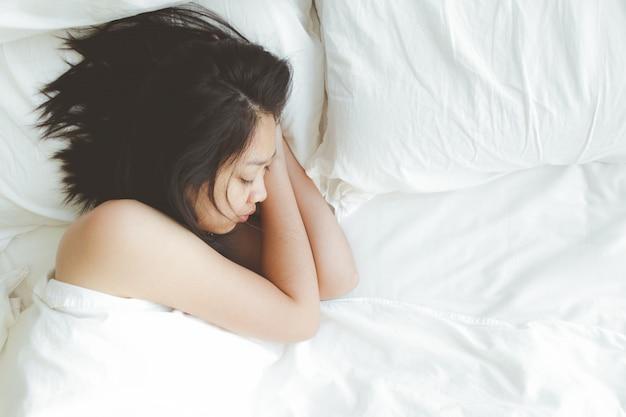 Frau hat einen tiefen schlaf auf weißem bett. konzept von versucht und ausruhen.