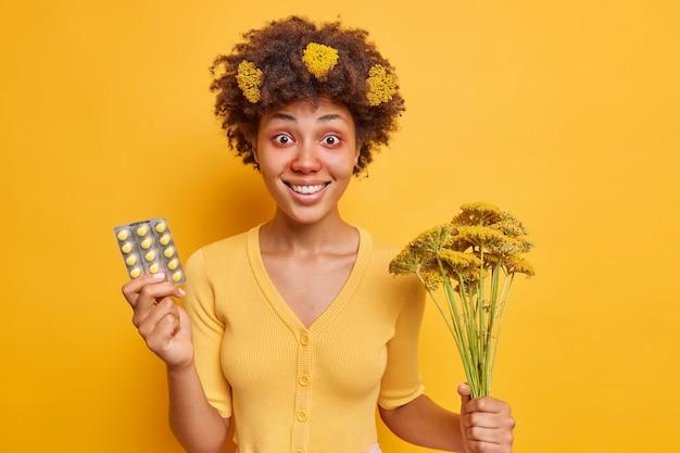 Frau hat endlich einen ausweg gefunden, kaufte wirksame pillen gegen saisonale allergie, die gegen pollen allergisch ist, hält einen strauß wilder blumen und hat rote geschwollene augen, die über gelber wand isoliert sind