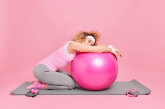Frau hat erschöpften blick lehnt sich an fitnessball im bodysuit bekleidet verwendet sportgeräte zum training