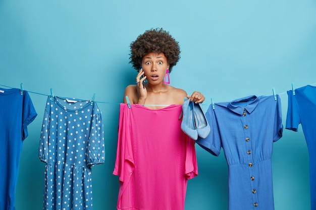 Frau hat fassungslose ausdrücke, die wenig zeit haben, um sich auf die party vorzubereiten, wählt kleid, das zu neuen schuhen passt, hat telefongespräch isoliert auf blau