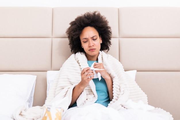Frau hat grippe und sie benutzt thermometer. . krank mit einer rhinitis-frau, die nase tropft. frau, die krank ist, die grippe liegend auf sofa liegt und temperatur auf thermometer betrachtet.