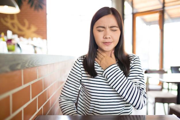 Frau hat halsschmerzen im cafe