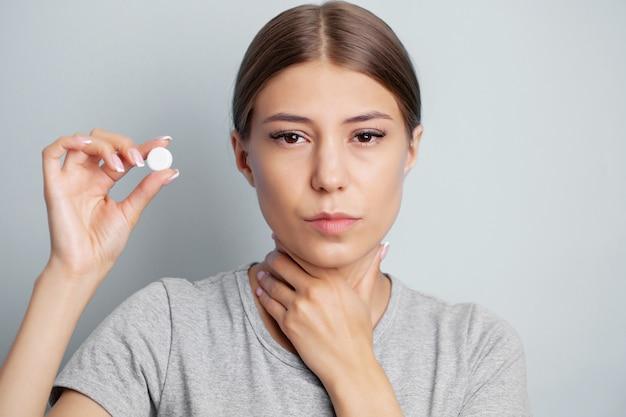 Frau hat halsschmerzen und hält eine pille zur behandlung