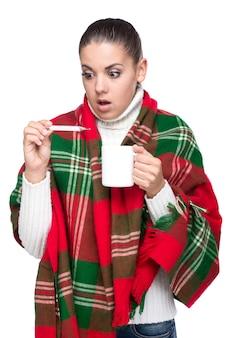 Frau hat hohe temperatur und hält eine tasse tee.